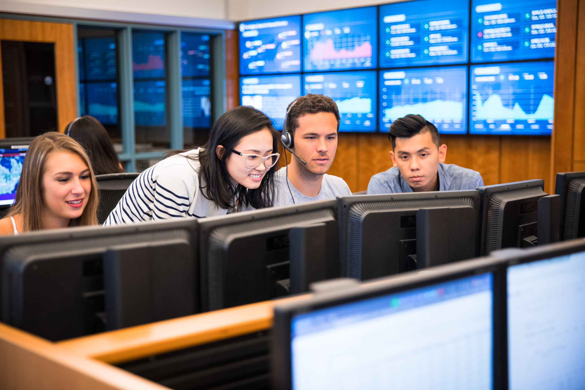 four students work in the trading room