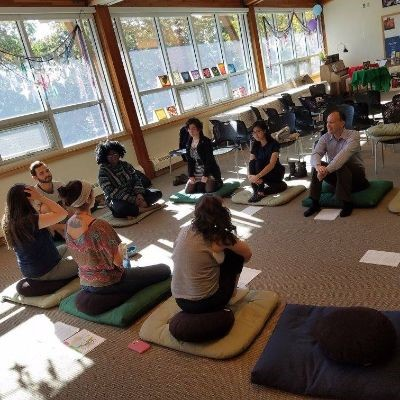 A group of people practice meditation in the Sacred Space.
