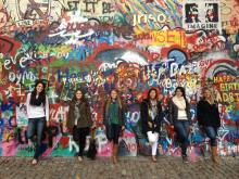 Six bentley students stand against a colorful graffiti wall in Prague, Czech Republic