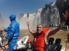Bentley Student smiles with life jacket on a boat, in front of iguazu Falls in Brazil