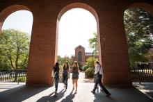 three bentley students walking through building on campus