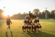 bentley students in human pyramid on lacrosse field