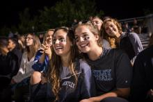two female students cheering on Bentley's football team