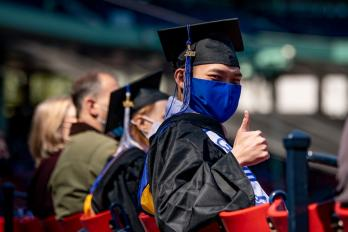 Student gives a thumbs up at the Bentley Commencement at Fenway Park 2021
