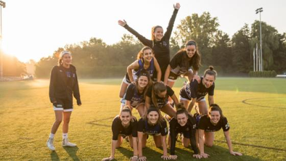women smile on lacrosse field while making human pyramid